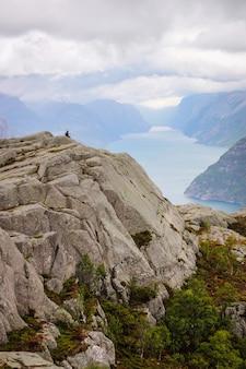 Alleinreisender des schattenbildes, der auf dem berg sitzt.
