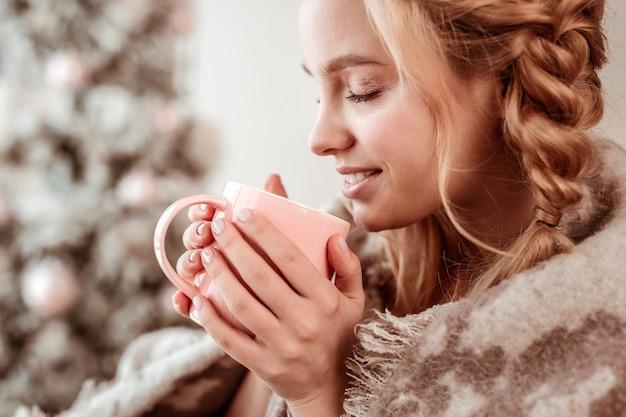 Alleinsein. meditative blonde dame, die heißes getränk von rosa tasse nippt, während sie weiches und leichtes make-up hat