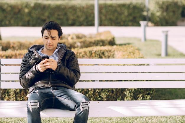 Alleinstehender mann, der auf der bank im park sitzt und mit dem telefon spricht. foto in hoher qualität