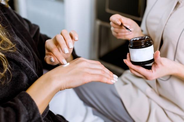Allergietest und kosmetologische beratung. professionelle kosmetikerin, die creme für ihre kundenhand gibt, während sie auf allergie getestet wird. kundin, die creme auf ihre hand aufträgt