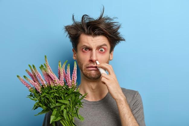 Allergischer mann hat unordentliche frisur, rote juckende augen, hält pflanze, die niesen oder steifheit verursacht, leidet an unangenehmen symptomen, hat behandlung zu hause, steht gegen blaue wand. nasenausfluss