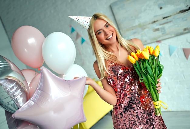 Alles gute zum geburtstag! glückliches mädchen mit gelben tulpen. party zum schönen mädchengeburtstag, das zimmer ist mit luftballons dekoriert.