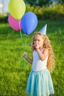 Alles gute zum geburtstag im park. ein kleines mädchen hat an ihrem geburtstag spaß mit luftballons und einer pfeife.