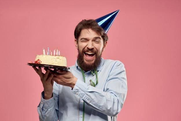 Alles gute zum geburtstag! junger mann mit einem festlichen kuchen mit scheiben feiert einen geburtstag in einer kappe