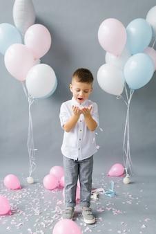 Alles gute zum geburtstag, kind. foto des entzückenden süßen kleinen jungen, der auf konfetti auf dem hintergrund von luftballons bläst