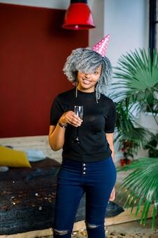 Alles gute zum geburtstag. mädchen mit konfetti und champagner auf der party. porträt der schönen lächelnden afrikanischen frau im geburtstagshut, der champagner in den händen hält, feiert feiertag. hohe auflösung.