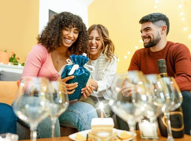 Alles gute zum geburtstag mit gemischtrassigen echten menschen zu hause, die lachen und mit champagner feiern