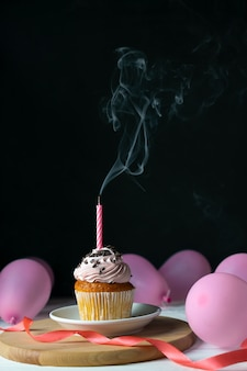 Alles- gute zum geburtstagkleiner kuchen mit einer kerze, die heraus auf schwarzem mit ballonen durchgebrannt wird.