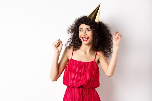 Alles- gute zum geburtstagmädchen feiern, partyhut und rotes kleid tragend, tanzend und spaß habend, vor weißem hintergrund stehend.