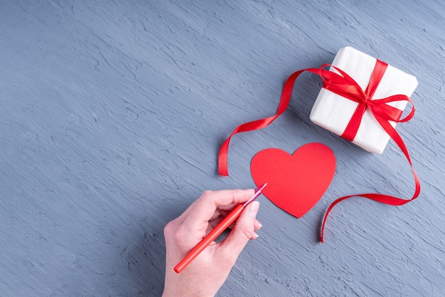 Alles gute zum valentinstag. hand hält einen roten stift, um einen valentinstag und ein geschenk in weißem geschenkpapier zu unterschreiben