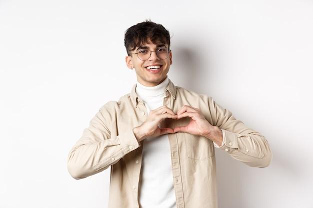Alles gute zum valentinstag. hübscher junger mann mit brille sagt, ich liebe dich, zeigt ein herzzeichen und lächelt die freundin an, feiert den tag der liebenden und steht auf weißem hintergrund