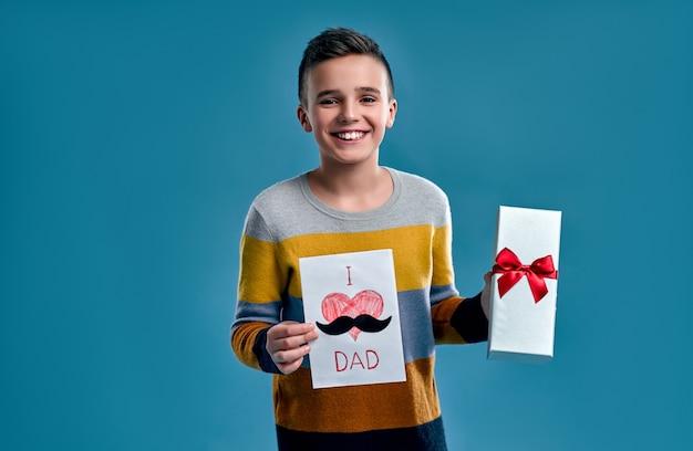 Alles gute zum vatertag! ein gutaussehender junge in einem gestreiften mehrfarbigen pullover hält eine geschenkbox und eine karte für seinen vater isoliert auf blauem hintergrund.
