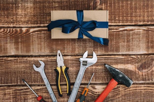 Alles gute zum vatertag. geschenkbox mit reparaturwerkzeugen, flachgelegt. hammer, zange, schraubenschlüssel, schraubendreher.