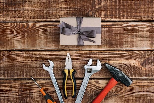 Alles gute zum vatertag. geschenkbox und reparaturwerkzeuge, flachgelegt. hammer, zange, schraubenschlüssel, schraubendreher.
