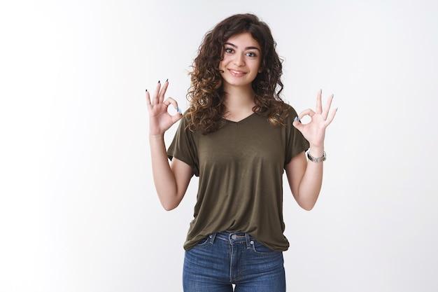 Alles in ordnung, keine sorge. portrait selbstbewusste, freundliche, fröhliche junge kaukasische, lockige frau, die lächelt und versichert, dass das geschäft in ordnung ist, stehender weißer hintergrund stimmt dem zufriedenen ergebnis zu