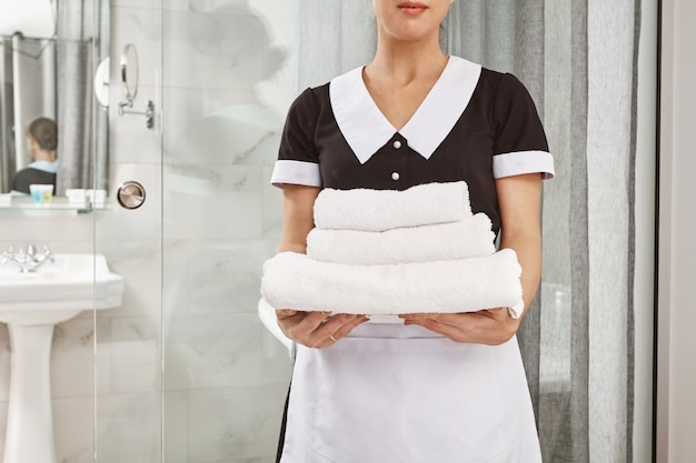 Alles ist frisch und sauber. beschnittenes porträt des hausputzers in der dienstmädchenuniform, die packung der weißen handtücher hält. der mitarbeiter brachte alles, was der kunde bestellt hatte, in sein hotelzimmer