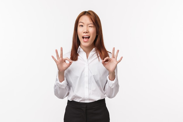 Alles ist gut. erfreute und zufriedene asiatische frau in weißem formellem hemd, augenzwinkern und lächeln zeigen okay geste, keine große sache, geben sicherheit und garantieren gute produktqualität, keine sorge