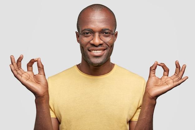 Alles ist ok! zufriedene glatze mit positivem lächeln, gesten drinnen, gekleidet in lässiges gelbes t-shirt