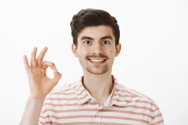 Alles ist okay. fröhlicher, freundlich aussehender kaukasischer kerl mit schnurrbart und bart, der mit ok oder großer geste die hand hebt, zustimmung oder ähnliches gibt und die situation unter kontrolle hat