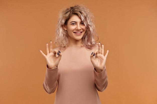 Alles ist perfekt. horizontal der freundlich aussehenden charmanten jungen frau mit piercing im gesicht und rosa haaren, die positive emotionen ausdrücken und breit lächeln