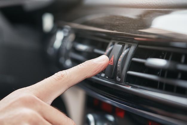 Alles ist perfekt in meinem auto beschnittenes bild einer hand, die auf den knopf drückt