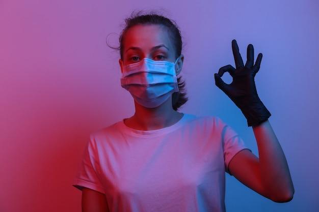 Alles ist unter kontrolle. entspannte frau in medizinischer maske und handschuhen zeigt ein ok-symbol. rot-blaues neonlicht mit farbverlauf