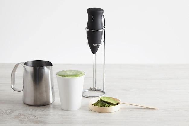 Alles notwendig, um latte auf moderne weise zuzubereiten. verkaufspräsentation. elektrischer milchschäumer auf chromständer, bio-premium-matcha-teepulver japan, papierglas zum mitnehmen, stahlmilchtopf für cappuccinato