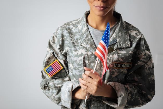 Alles schützen, was ich liebe. zuversichtlich starke wunderbare frau, die eine uniform trägt und eine fahne in ihren händen hält