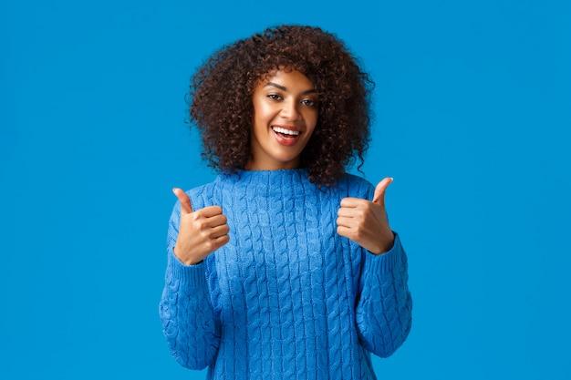 Alles super cool. nette und erfüllte afroamerikanerfrau mit afrohaarschnitt, lächelnd und zeigen thumbs-up in der zustimmung, wie das produkt, empfehlen die software oder app und stehen blau
