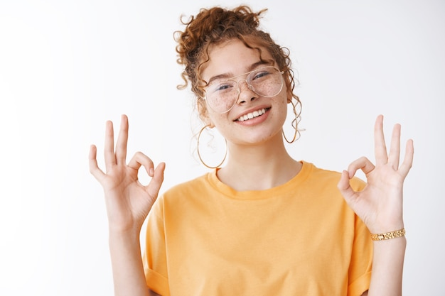Alles super. portrait charmant chillig selbstbewusst glücklich lächelnde rothaarige mädchen mit brille orange t-shirt kippender kopf grinsend selbstbewusste show okay ok kein problem geste weißer hintergrund