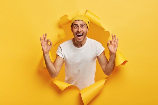 Alles unter kontrolle. erfreuter glücklicher mann gibt positive meinung, macht okay geste mit beiden händen