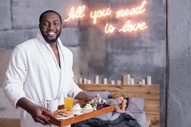 Alles, was sie brauchen, ist liebe. afrikanischer junger entzückter mann, der das tablett hält, während frühstück für seine frau vorbereitet und lächelt.