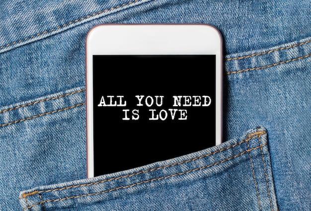 Alles, was sie brauchen, ist liebe am hintergrund telefon auf jeans liebe und valentinstag konzept