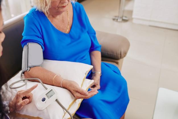 Allgemeinarzt, der den blutdruck des patienten überprüft