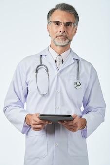 Allgemeinarzt mit stethoskop über den schultern, die den digitalen vorsprung halten und kamera betrachten