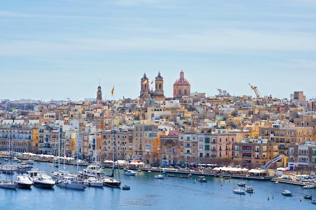 Allgemeine ansicht über birgu-stadtufergegend und -skyline in der bucht mit bunten booten in malta.