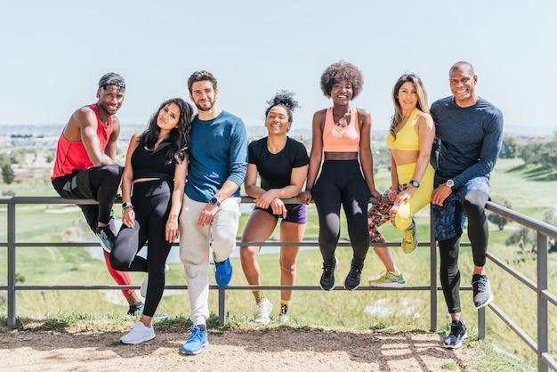 Allgemeine aufnahme einer gruppe von läuferfreunden, die in einem park lächelnd in die kamera schauen