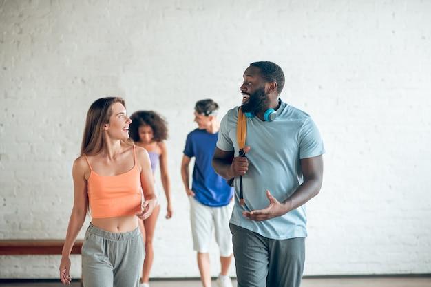 Allgemeines interesse. junger und athletischer bärtiger afroamerikanermann mit rucksack und blondem mädchen, das nach dem training kommuniziert