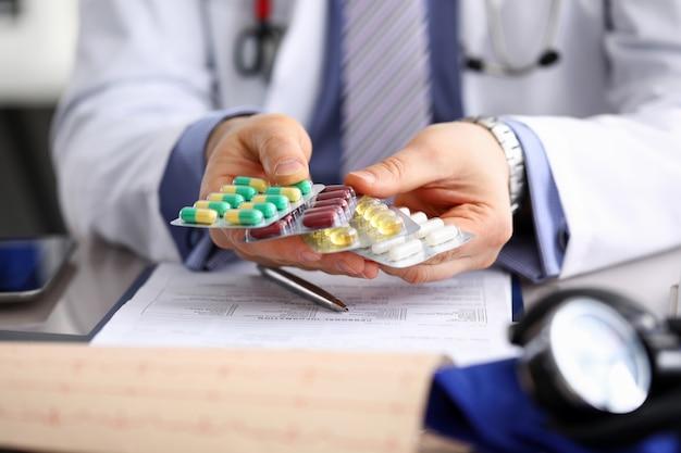 Allgemeinmediziner in der klinik hält packung mit verschiedenen blasen in nahaufnahme.