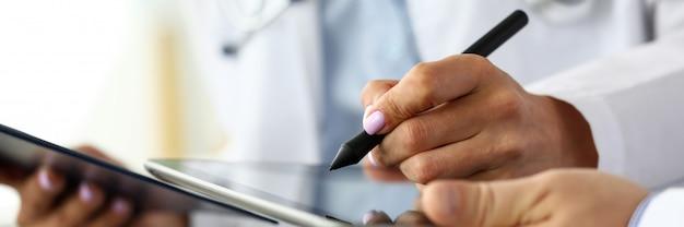 Allgemeinmedizinerin, die elektronische notizen im tablet-pc macht