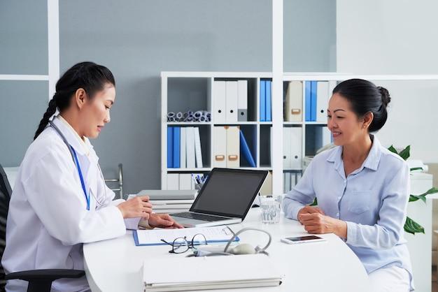 Allgemeinmedizinerin im gespräch mit der älteren patientin und ausfüllen des formulars mit ihren persönlichen daten und beschwerden