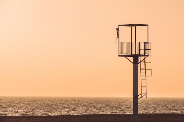 Almerimar-strandleibwächterturm bei sonnenuntergang.