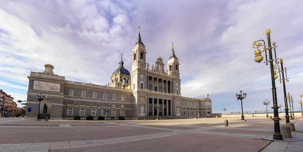 Almudena kathedrale in madrid und seine riesige promenade vor mit laternenpfählen und blauem himmel. spanien.