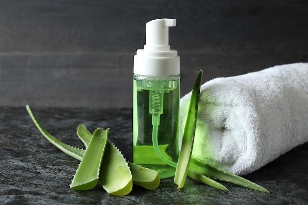 Aloe-blätter, kosmetik und handtuch auf schwarzem rauchtisch