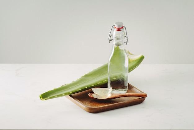 Aloe-stücke, frische blätter und flaschenglas auf weißem hintergrund