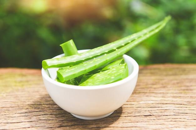 Aloe vera-betriebsscheibe in der schüssel nah oben vom frischen aloe vera-blatt mit natürlichen kräutern des gels und kräutermedizin