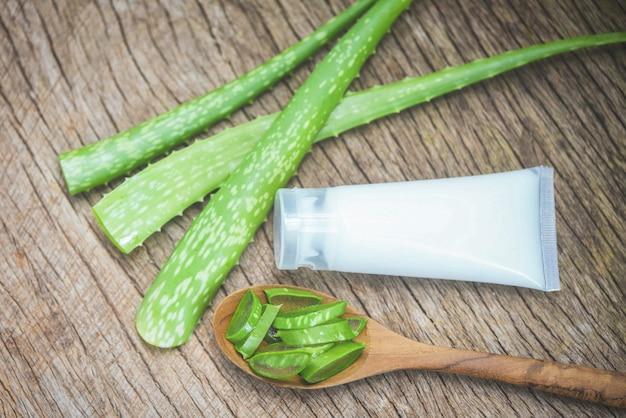 Aloe vera-betriebsscheibe und lotionsflasche auf rustikalem hölzernem hintergrund / frischem aloe vera treiben mit natürlichen kräutern des gels und kräutermedizin blätter