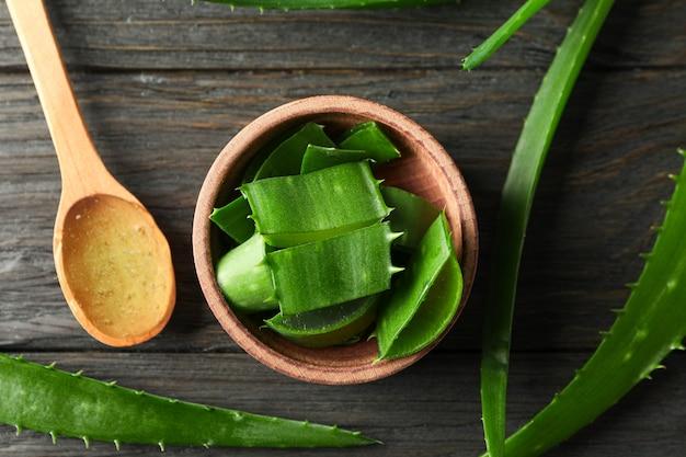 Aloe vera blätter und scheiben auf holztisch, nahaufnahme und draufsicht. natürliche behandlung