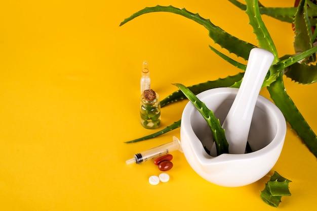 Aloe vera blatt, weißer mörtel voll gehackter aloe und flaschen aloe gel oder infusion.