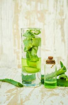 Aloe vera-extrakt in einer kleinen flasche und auf dem tisch. selektiver fokus